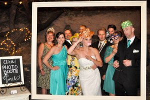 Katy and Tim and their family in the photo booth frame.